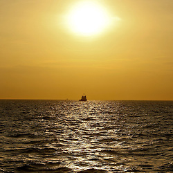A support vessel passes under the sun at sunrise at the BP Plc Macondo well site in the Gulf of Mexico off the coast of Louisiana, U.S., on Friday, July 30, 2010. BP Plc continues to work on a relief well to permanently plug the source of the largest oil spill in U.S. history.  Photographer: Derick E. Hingle/Bloomberg