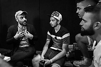 """NAPLES, ITALY - 30 JULY 2018: Roberto Saviano (left), an Italian journalist, writer and essayist chats with the young actors of the collective """"Nuovo Teatro Sanità"""" (New Sanità Theatre) in the Sanità neighborhood in Naples, Italy, on July 30th 2018.<br /> <br /> In 2017 the 17-year-old innocent victim Genny Cesarano was shot and killed by stray bullet  in cross fire between 2 rival gangs vying for territorial control in the Sanità neighborhood.<br /> The  isolation of the neighborhood Sanità over the years provided an ideal location for the Camorra to expand their illicit activities and profit from soaring unemployment rates and economic instability,<br /> <br /> After the first death threats of 2006 by the Casalese clan , a cartel of the Camorra, which he denounced in his exposé and in the piazza of Casal di Principe during a demonstration in defense of legality, Roberto Saviano was put under a strict security protocol. Since 2006 Roberto Saviano has lived under police protection.<br /> <br /> Saviano's latest novel """"The Piranhas"""", which tells the story of the rise of  a paranza (or Children's gang) and it leader Nicolas, will be released in the United States on September 4th 2018."""