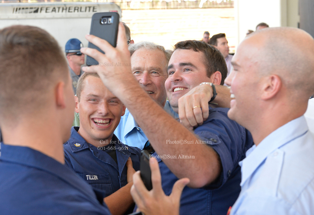 "Gulfport, MS 8/28/15 President Bush poses for ""selfies"" with  Mississippi first responders during the 10th Anniversary Hurricane Katrina event in Gulfport. Mississippi. Governor Phil Bryant checks the morning papers as he waits for  the 10th Anniversary Hurricane Katrina event. to begin. President George Bush joined Mississippi Governor's Haley Barbour and Governor Phil Bryant  for a first responders event to commemorate the 10th Anniversary of Hurricane Katrina in Gulfport Mississippi. Photo ©Suzi Altman"