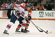 RIT's Caleb Cameron and Brock University's Daniel Tanel fight for a loose puck during a game at the Gene Polisseni Center on Saturday, October 4, 2014.