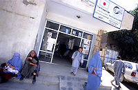 KABUL 15 August 2005..Women sit around the doorway  of Maiwand Hospital RSU.....Shabana. a nine months old Afghan girl, has been diagnosed with a 'neurofibroma'. This is a tumor or growth located along a nerve or nervous tissue. It is an inherited disorder. If left unchecked, a neurofibroma can cause severe nerve damage leading to loss of function to the area stimulated by that nerve.....The Rehabilitative Surgery Unit (RSU) at Maiwand Hospital is fully supported by the French NGO Medical Refresher Courses for Afghans (MRCA), also by the French Minister of Foreign Affairs, and by the Embassy of Japan under the Grant Assistance for Grassroots Project (GAGP). The Italian NGO Operation Smile Italia Onlus provides training to the Doctors. ....Maiwand Hospital dates back to the rein of Nadir Shah in the 1930s.