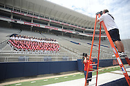 Ole Miss photographer Josh McCoy (right) takes the team photo during the team's media day, at Vaught-Hemingway Stadium in Oxford, Miss. on Friday, August 1, 2014. Mississippi begins practice Saturday morning and opens the season against Boise State in Atlanta on August 28, 2014.