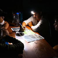 Julio Araújo, Field and Laboratory Coordinator at CINCIA looks over maps at the Balata military base with his team to plan the next days survey of mining ponds. Following Peru's February 2019 militarized crackdown on illegal and unofficial alluvial gold mining in the La Pampa region of Madre de Dios, Wake Forest University's Puerto Maldonado-based Centro de Innovación Científica Amazonia (CINCIA), a leading research institution for the development of technological innovation for biological conservation and environmental restoration in the Peruvian Amazon, is applying years of scientific research and technical experience related to understanding mercury contamination and managing Amazonian ecosystems. What they learn will help guide urgent remediation, restoration, and reforestation efforts that can also serve as models for how we address the tropic's most dramatically devastated landscapes around the world. La Pampa, Madre de Dios, Peru.