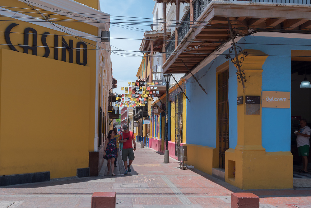 Santa Marta, Columbia-- April 22, 2018. Photo of pedestrians on a brightly colored side street in Santa Marta, Columbia. Editorial use only.