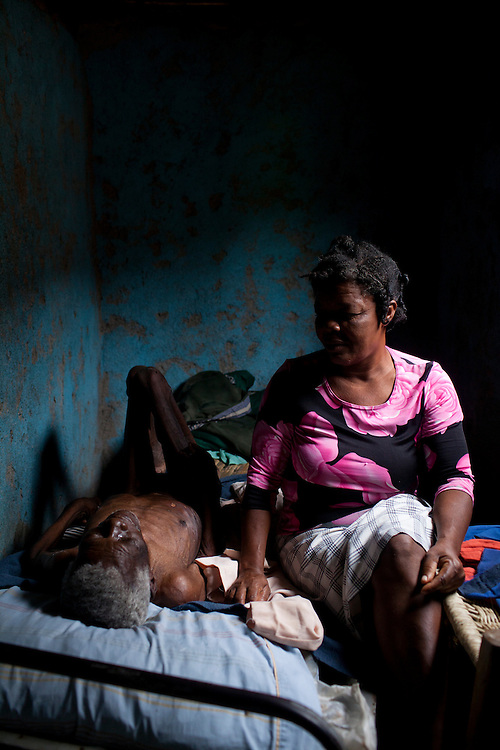 Lauredan Timerci lies dying in bed at around 80 years of age as his daughter Rosette Louredan comforts him on July 16, 2010 in Gador, Haiti.