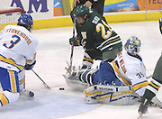NMU's Mark Olver (21) and LSSU's Dillin Stonehouse (3) battle for a loose puck that gets behind Lakers goalie Brian Mahoney-Wilson (35) during the third period Saturday at Taffy Abel Arena in Sault Ste. Marie.