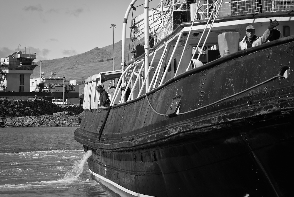 A seaman gestures from the bow of an old tugboat in front of the cargo terminal, Lyttelton Harbour, New Zealand