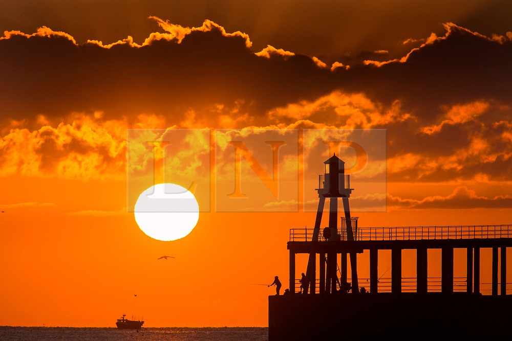 © Licensed to London News Pictures. 18/07/2018. Whitby UK. People fish from the end of Whitby pier this morning as the sun rises on the Yorkshire coast & the UK prepares for another hot day. Photo credit: Andrew McCaren/LNP