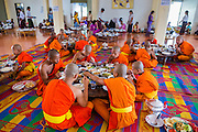 24 MAY 2013 - MAE SOT, THAILAND: Burmese novice monks participate in the communal meal after Visakha Puja services at Wat Pha Mai. Visakha Puja (Vesak) marks three important events in the Buddha's life: his birth, his attainment of enlightenment and his death. It is celebrated on the full moon of the sixth lunar month, usually in May on the Gregorian calendar. This year it is on May 24 in Thailand and Myanmar. It is celebrated throughout the Buddhist world and is considered one of the holiest Buddhist holidays. Burmese Buddhist in Mae Sot celebrated with a procession through Mae Sot that ended with a service followed by a communal meal at Wat Pha Mai, the most important Burmese Buddhist temple in Mae Sot.      PHOTO BY JACK KURTZ