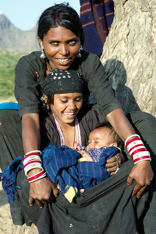 Mother from the Bhopa community with two children sitting on her lap, leaning against a tree.