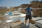 Tunisian Jew, Yossef Sabbagh. a member of the Hevra Kadisha religious committee responsible for burials ,as he stands by cracked marble tombstones that litter the outer perimeter of the cemetery behind the Great Synagogue of the tiny Tunisian Jewish community on the island of Djerba on May 27,2016. Vandals  did not break the gravestones he said but instead the graves were exhumed and sent to Israel for reburial . (Photo by Heidi Levine).
