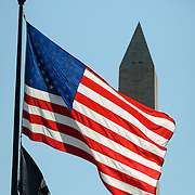 American Flag and Washington Monument. The American flag, backlit, in the foreground, with the top of the Washington Monument in the background.