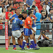 Manu Samoa players embrace Tila Mealoi, who scored the winning try to beat the New Zealand All Black 7's 26-21, earning the Plate Final at the HSBC Singapore 7's, day 2, Singapore National Stadium, Singapore.  Photo by Barry Markowitz, 4/17/16