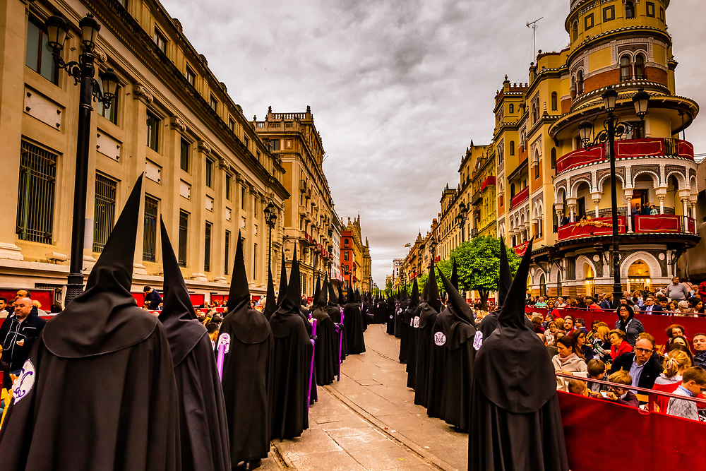 Hooded Penitents (Nazarenos) in the procession of the Brotherhood (Hermandad) San Bernardo,  on Avenue de la Constitucion (with the rounded Adriatic Building (Edificio de la Adriatica) behind, Holy Week (Semana Santa), Seville, Andalusia, Spain.