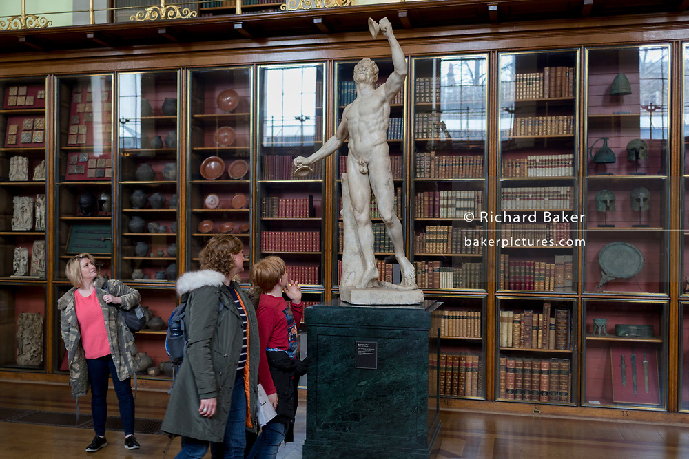 Visitors admire the sculpture of Rondanini's Faun - a 2nd century Roman copy of a Greek original - in the Enlightenment Gallery of the British Museum, on 11th April 2018, in London, England.