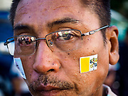 30 NOVEMBER 2017 - YANGON, MYANMAR: A man with a Vatican flag sticker on his cheek during the Papal Mass at St. Mary's Cathedral in Yangon. Thursday's mass was his last public appearance in Myanmar. From Myanmar the Pope went on to neighboring Bangladesh.   PHOTO BY JACK KURTZ