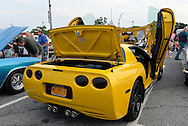 Bellmore, New York, USA. 12th June 2015. A modified yellow 2003 Corvette 50th Anniversary model, with Lamborghini doors (AKA vertical scissors doors and Lambo doors) and chrome trim added to inside of hood to reflect engine, an award winning car owned by Grey Cherveny of Bay Shore, is displayed  at the Friday Night Car Show held at the Bellmore Long Island Railroad Station Parking Lot. Hundreds of classic, antique, and custom cars were on view at the free weekly show, sponsored by the Chamber of Commerce of the Bellmores.