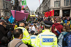 London, UK. 18th April 2019. Police officers move in to arrest climate change campaigners from Extinction Rebellion as part of a large police operation to try to clear Oxford Circus of protesters on the fourth day of International Rebellion activities to call on the British government to take urgent action to combat climate change.