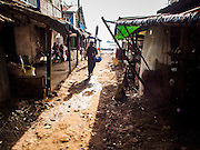 10 NOVEMBER 2014 - SITTWE, MYANMAR: A woman walks down a street near the waterfront in Sittwe. Sittwe is a small town in the Myanmar state of Rakhine, on the Bay of Bengal.    PHOTO BY JACK KURTZ