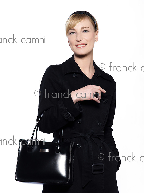 beautiful blond caucasian <br /> woman on studio white background with black overcoat and purse