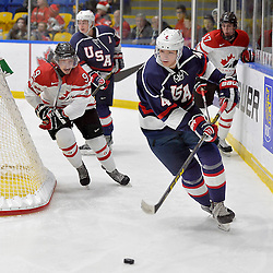 WHITBY, - Dec 18, 2015 -  Game #12 - Bronze Medal Game, Team Canada East vs. United States at the 2015 World Junior A Challenge at the Iroquois Park Recreation Complex, ON.  John Marino #4 of Team United States skates with the puck while being pursued by &Eacute;douard Michaud #9 of Team Canada East during the second period.<br /> (Photo: Shawn Muir / OJHL Images)