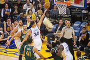 Golden State Warriors guard Stephen Curry (30) lays the ball up against the Utah Jazz at Oracle Arena in Oakland, Calif., on December 20, 2016. (Stan Olszewski/Special to S.F. Examiner)