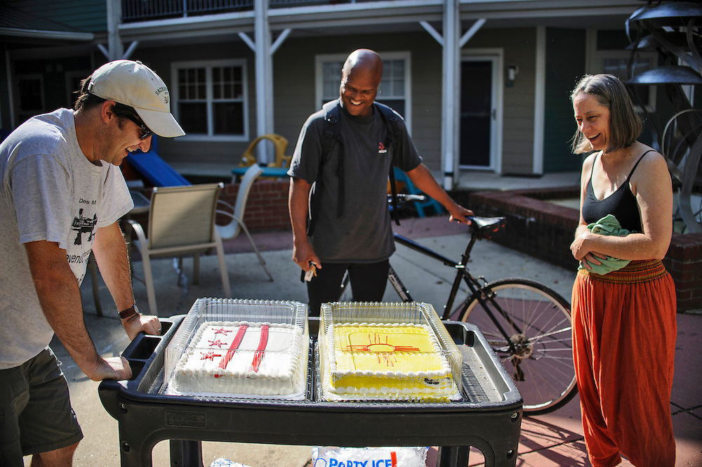 photo by Matt Roth..Norton Francis, left, and married couple Bruce Jones, middle, and Robbin Phelps, right, comment on the two cakes Norton wheels through Takoma Village Cohousing's courtyard Saturday, September 22, 2012. Later that day Norton and his wife Anne Stauffer, who transplanted from New Mexico to D.C., are throwing a Green Chile Party for friends and neighbors. One cake is the D.C. flag and the other is the New Mexico Flag.