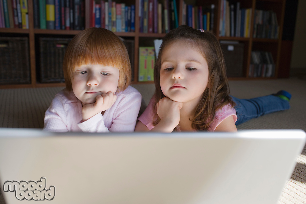 Young girls (5-6) lying on floor using laptop contemplating with hand on chin