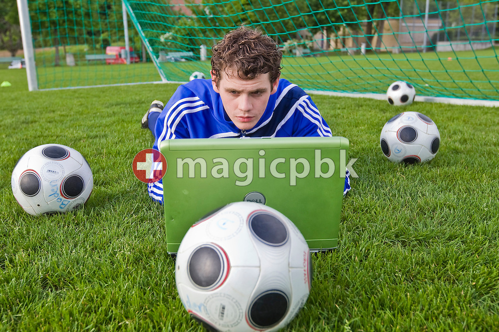 FC Baden A-Junior soccer goalkeeper Marco Maeder of Switzerland types on his laptop while lying on the ground in a goal surrounded by balls during a training session in Ruetihof near Baden AG, Switzerland, Friday, May 25, 2010. Fifa bans the use of social network platforms like Facebook in their venues during the Fifa World Cup 2010 in South Africa. (Photo by Patrick B. Kraemer / MAGICPBK)