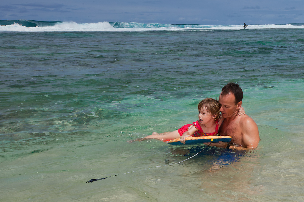A father teaching his daughter how to boogie board on the beach in Hawaii