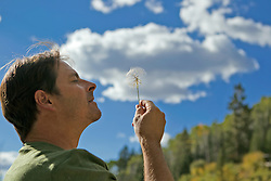 man blowing a milkweed towards the sky in Santa Fe