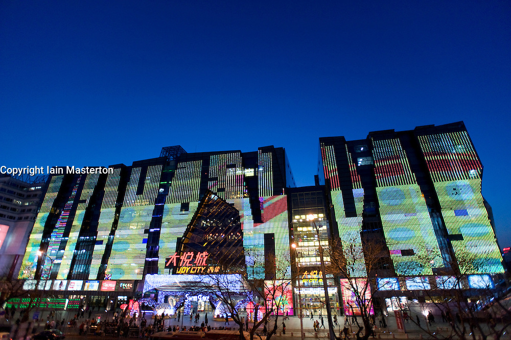 Evening view of exterior of large new modern shopping mall called Joy City in Xidan district Beijing 2009