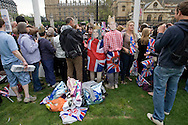 A couple wearing William and Kate masks in Parliament Square, London, awaiting the arrival of guests and members of the British royal family prior to the wedding of Prince William to Catherine Middleton. The wedding was held at Westminster Abbey. Tens of thousands of people lined the streets to wish the couple well before and after the ceremony.