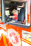 Toddler holding steering wheel in cab of fire truck. Aquatennial Beach Bash Minneapolis Minnesota USA