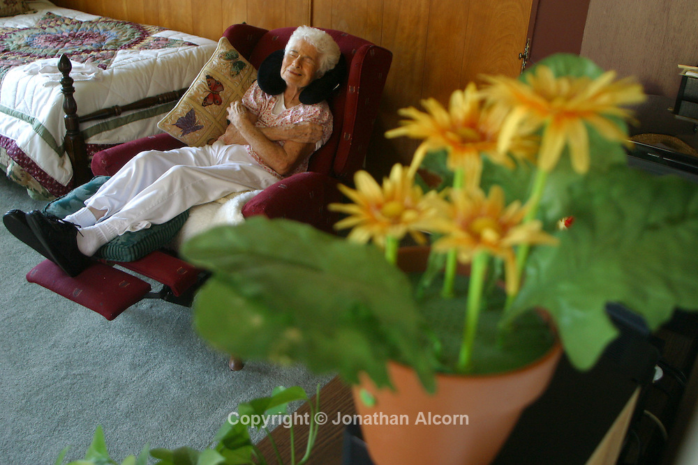 A woman with Alzheimers sits in a chair while weeping at a live-in residence for Alzheimer's and dementia related  patients.