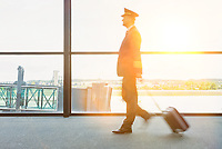 Portrait of mature pilot walking in airport with yellow lens flare