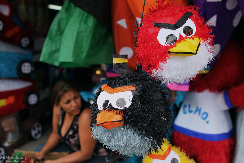 A piñata vendor waits for customers underneath piñatas of the angry birds characters near Colón Park in Zone 1. Guatemala City, Guatemala. April 26, 2013.