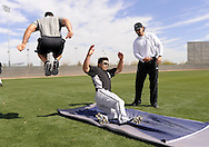 GLENDALE, AZ - FEBRUARY 25:  Carlos Quentin #20 of the Chicago White Sox practices sliding as strength coaches Allen Thomas (L) and Dale Torborg look on during a spring training workout on February 25, 2011 at Camelback Ranch in Glendale, Arizona. (Photo by Ron Vesely)