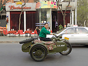 man driving an old US Army motorcycle with sidecar while passing a Budweiser bar China Beijing