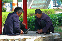 China, Taiyuan, 2008. Summertime sees lots of people outside enjoying themselves, including these two poor men playing chess with an improvised board..