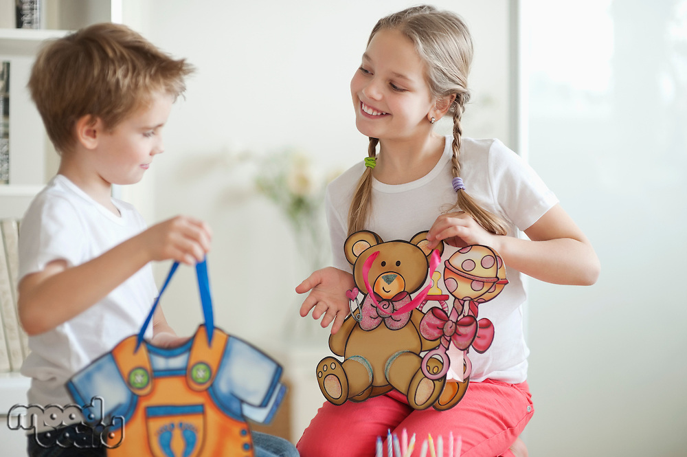 Young boy and girl holding their toy bags