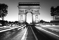 Black and White photograph Arc de Triomphe, Paris in early evening, with swirling traffic