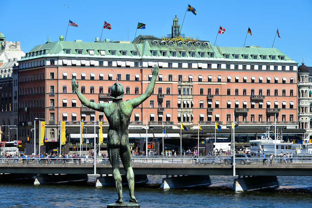 Sun Singer Statue at Str&ouml;mparterren Park in Stockholm, Sweden<br /> This statue of Apollo, the Greek god of the sun, poetry and music, appears to flashing the city of Stockholm because he is naked except for his helmet. Called the Sun Singer or Sols&aring;ngaren in Swedish, the giant bronze sculpture by Carl Milles stands proudly and unabashedly in Str&ouml;mparterren Park overlooking the Norrstr&ouml;m with the Grand H&ocirc;tel in the background.