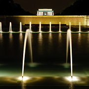 Night shot of the fountains of the National World War II Memorial with the Lincoln Memorial in the distance.