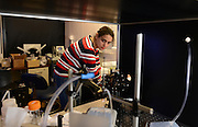 A graduate student in the physics program works in a lab in the Science Researh Building.