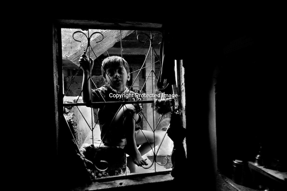 A boy looks into the window of a home near site of the Union Carbide plant behind him in the city of Bhopal in the state Madhya Pradesh, India, October 09, 2009. ..Twenty-five years after a gas leak in the Union Carbide factory in Bhopal killed at least eight thousand people, toxic material from the 'biggest industrial disaster in history' continues to affect Bhopalis. A new generation is growing up sick, disabled and struggling for justice.