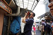 tourist photographing the menu display of a sushi restaurant at Tsukiji fish market Tokyo, Japan.
