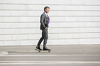 Businessman skateboarding on street