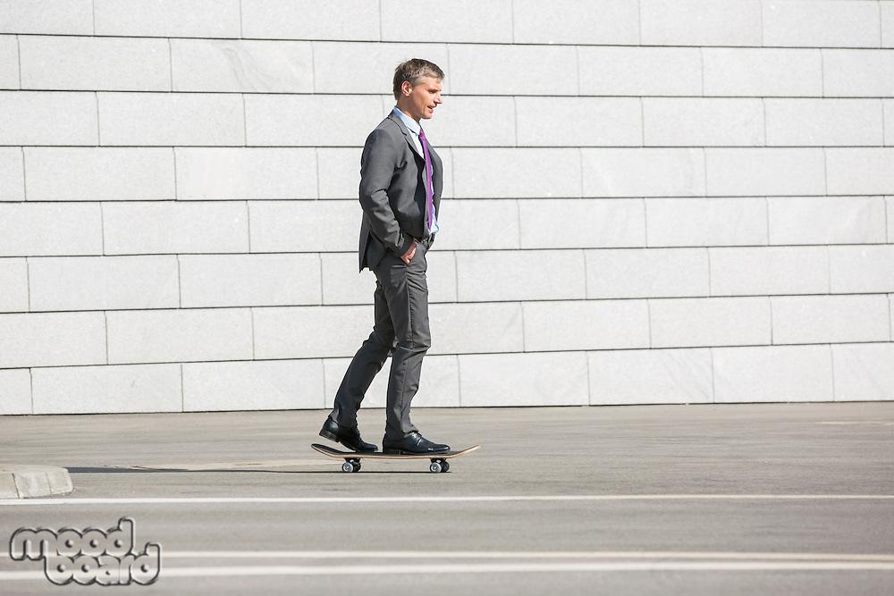 Businessman skateboarding on street