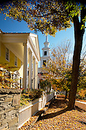 A view of autumn foliage and a colonial style house and church on Main Street in Rensselaerville, New York, U.S.A.